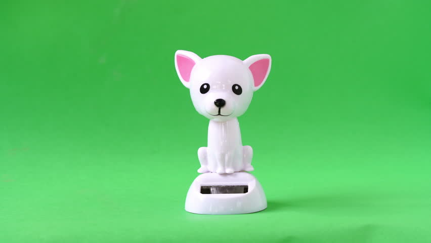 White dog doll dancing on green screen background.
