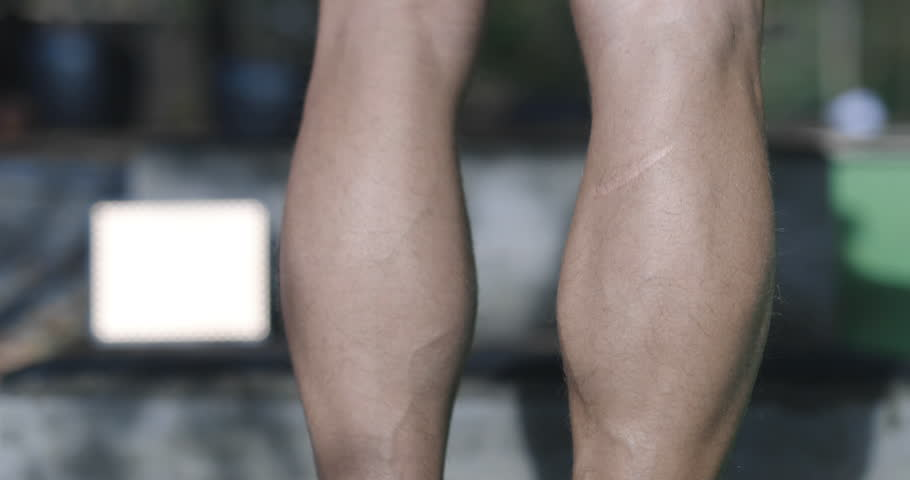 Close up shot of man doing calf raise exercise on his right leg. Great muscle flex. | Shutterstock HD Video #1022721730