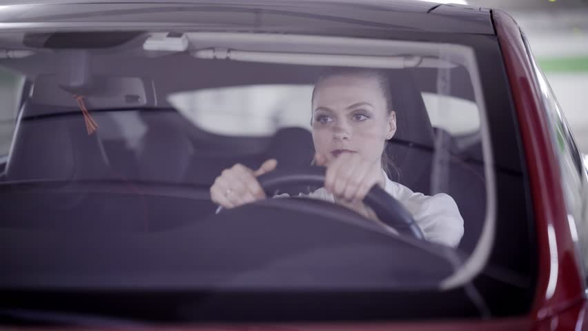 Beautiful young blonde woman with pony tail wearing white classic shirt sitting in red car behind steering wheel and looking around in underground garage.