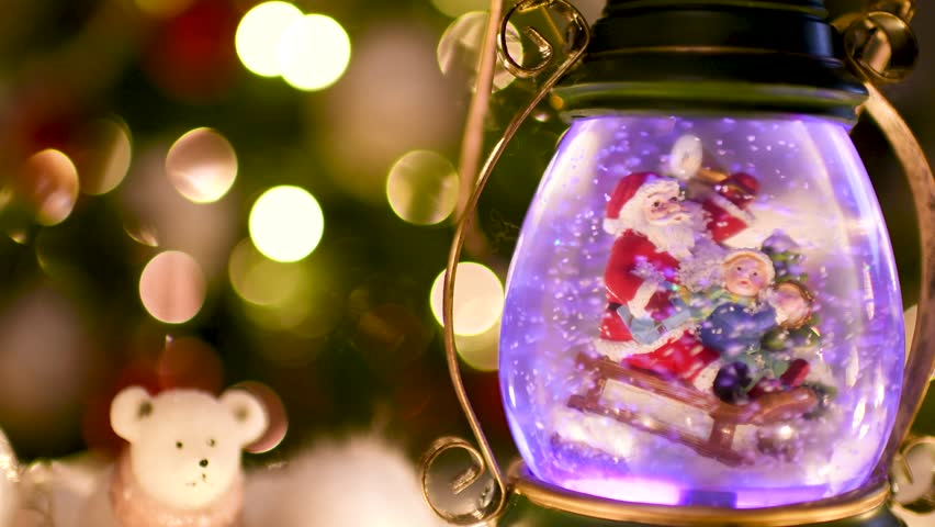 Cute color change snow globe with Santa Claus and child on sleigh with Christmas lights blurred in the background. Flat plane