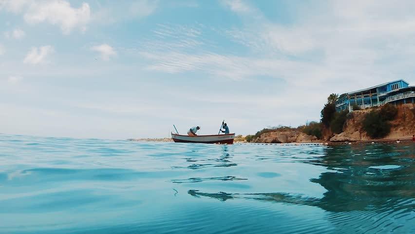 Two fishermen in boat working fishing net near Caribbean beach, SLOWMO #1022778550