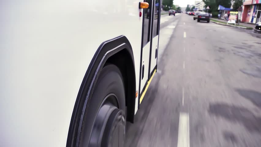 Close up view from the wheels and tires on the road of a bus riding around town, time laps. Scene. White bus moves down the street in the center of the city. | Shutterstock HD Video #1022812540