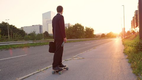SLOW MOTION, SUN FLARE: Young man in a black suit riding his skateboard down the empty pavement and into the golden sunset. Unrecognizable sporty businessman going home on his cool electric longboard.