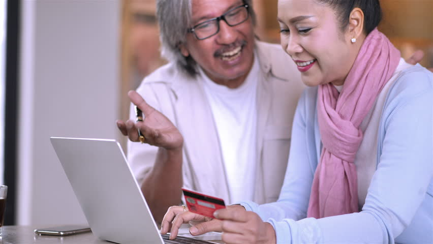 Senior Asian Couple at home connected on laptop computer and Credit card. Financial Transactions,Banking or online shopping concept. Slow Motion | Shutterstock HD Video #1022861950