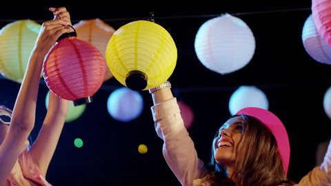 Two young girls decorating yard with chinese colorful lanterns. Colorful balls hanging from electrical wires. Preparation before birthday party. Shot on RED EPIC Cinema Camera in slow motion.   2