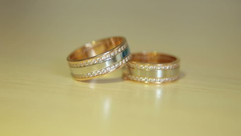 Gold engagement rings on beige background. Wedding Rings. Two splendid wedding rings on a wedding day. Two wedding rings on the table.