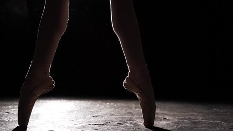 Beautiful leg in pointe shoes on black background. Ballet practice. Slow motion.