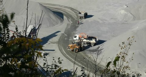 A bulldozer in a quarry pours cargo into a truck, loading a dump truck in a quarry