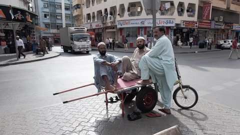 DUBAI UNITED ARAB EMIRATES - JANUARY 08 2019: Three people in Asian national clothes are sitting barefoot in a rickshaw (cart) near a busy intersection in one of the oldest districts of Dubai and look