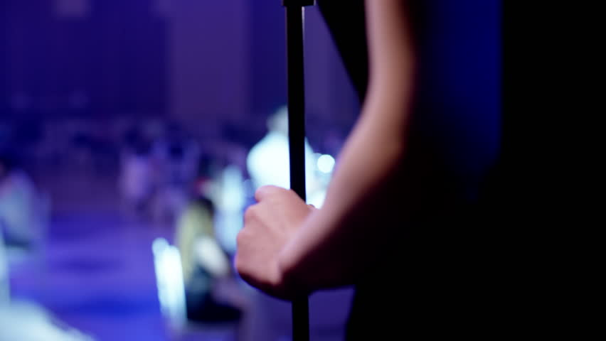 Rear or back view of a elegant woman singing to microphone on blur background .  Glamorous singer holding a mike and singing . Beauty glamour fashion woman with microphone over restaurant hall . | Shutterstock HD Video #1022940820