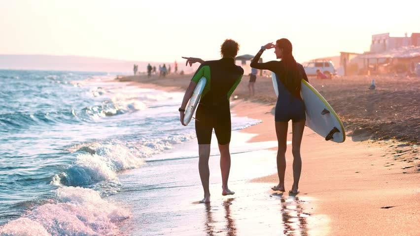 A young couple of guy and girl surfers are walking along the beach in wetsuits. In the hands of holding surfboards. Look at the waves and the sunset.