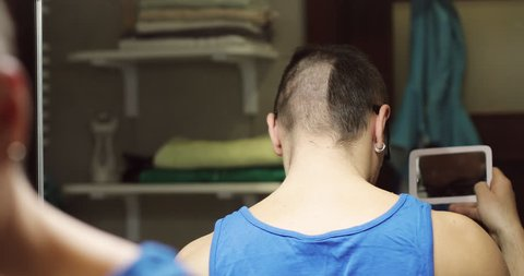 An adult man with a beard cuts his hair with an electric trimmer. Grooming the hair. Back view.