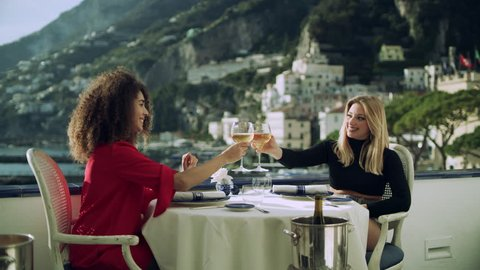 With a view of the Amalfi coast in the background, two beautiful chatty friends raise their glasses of wine and 'cheers'. Wide shot on 8k helium RED camera.