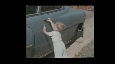 1954 Cute Blonde Baby boy running up and down hill next to antique vintage cars