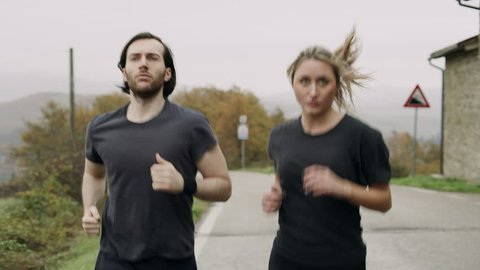Along a quiet street on an overcast day, an active Italian couple running along the street side by side. Medium shot on 8k helium RED camera.