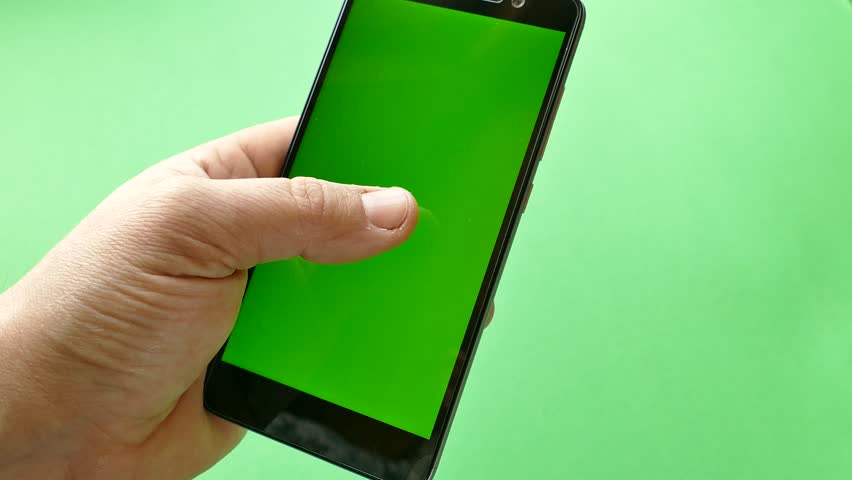 The smartphone is held in their hands and use it. Green screen in the phone on a green background. The girl is flipping through the pages in the gadget. Shop online. Shopping in the smartphone. Chrome