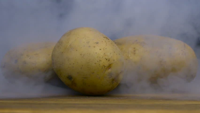 Russet potatoes are on the table and smoke or steam blows from behind in slowmo, cloese up | Shutterstock HD Video #1023028210