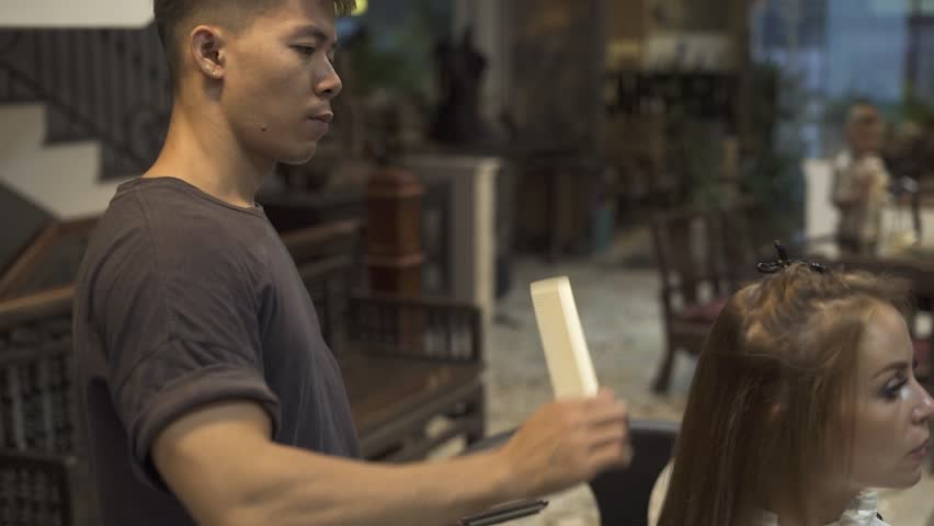 Hairdresser parting hair for straightening with iron in beauty salon. Hairstylist combing hair in hairdressing salon. Woman hairstyling in barbershop. Beauty and care. Female hairstyle concept | Shutterstock HD Video #1023028990