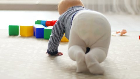 The baby girl learns to crawl, the first attempts to crawl. Baby crawls to the camera, smiling and laughing on the floor in the white room