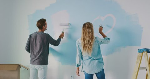Smiling couple painting heart on wall, new home improvement