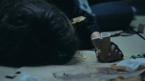 Drug intoxicated homeless woman sleeping on street full of garbage, addiction reenactment