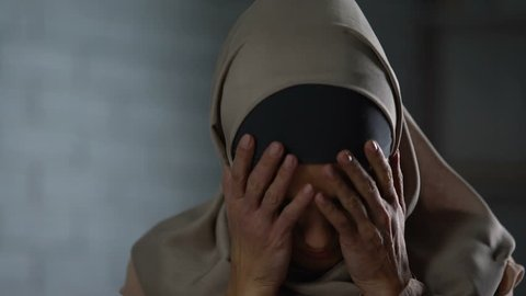 Desperate muslim woman crying, covering face with hands, family problem, shame