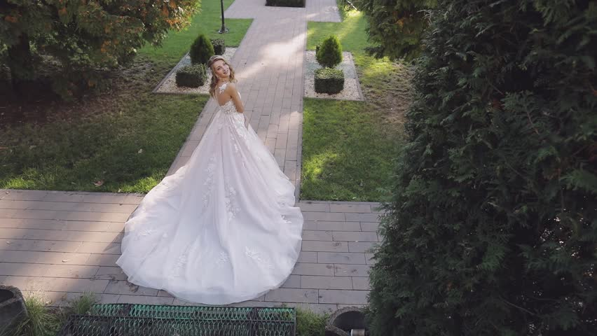Beautiful and lovely bride in the park. Pretty and well-groomed woman. Blonde. Wedding day. Slow motion | Shutterstock HD Video #1023105910