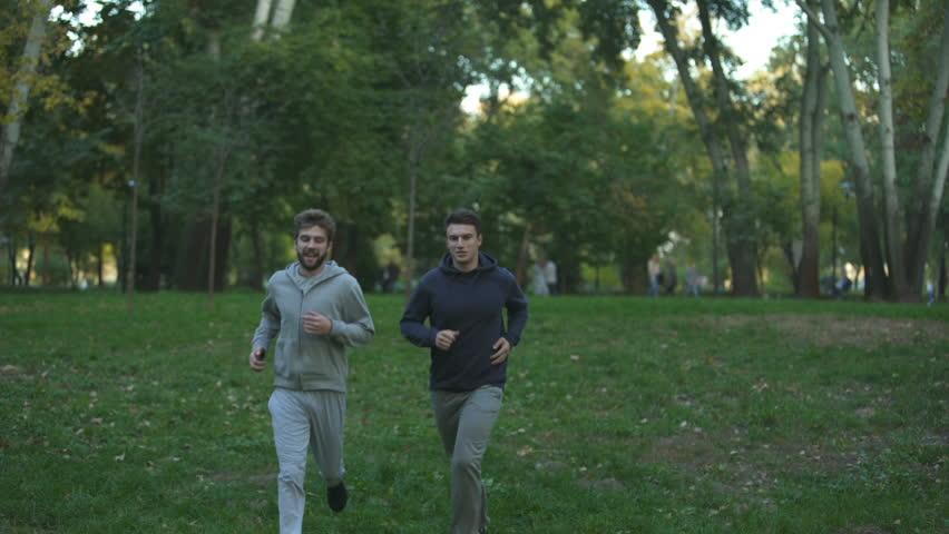 Homosexual couple jogging in park, evening training, discussing family issues | Shutterstock HD Video #1023108580