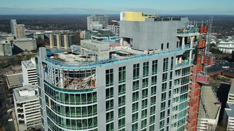 Tysons, VA / USA - December 29 2018: Descent down tall building under construction showing workmen inside and outside on Pinnacle Drive.