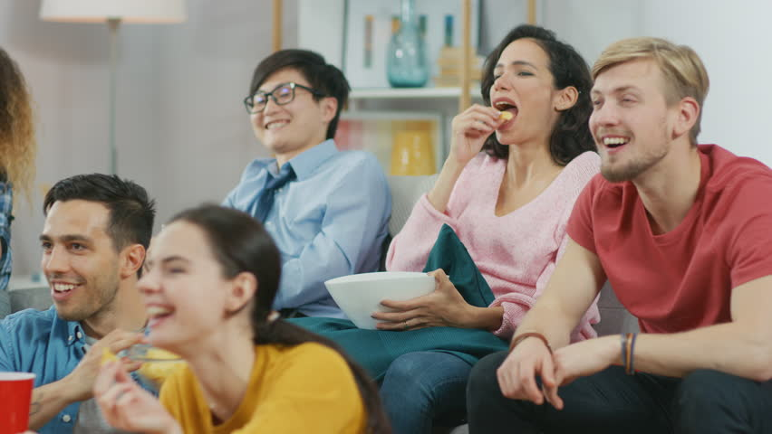 At Home Diverse Group Friends Watching TV Together, Eating Snacks and Drinking Beverage. Watching Comedy Sitcom or a Movie, Laughing and Having Fun Together. | Shutterstock HD Video #1023137800
