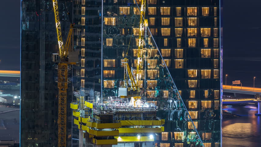 Construction site with cranes. Building of skyscrapers. Aerial top view with many workers and glowing windows on background | Shutterstock HD Video #1023183640
