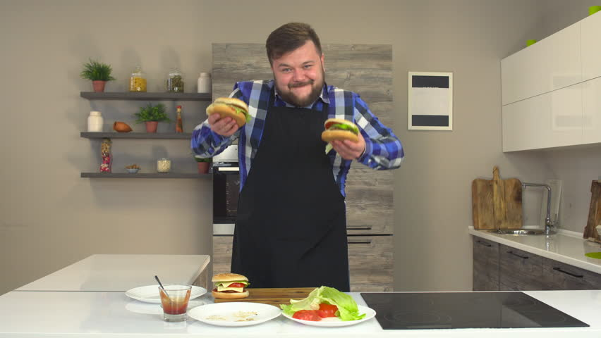 Satisfied fat man with a beard and apron dancing and smiling in the kitchen with burgers | Shutterstock HD Video #1023198700