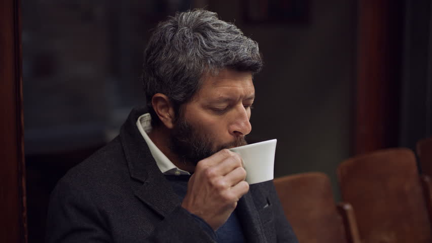 Portrait of an attractive Italian man drinking and enjoying a coffee from a white cup outside of a cafe. Close up shot on 8k helium RED camera.