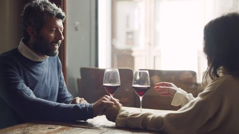 A loving Italian couple celebrate date night while sitting at a table in a restaurant as a waiter pours them red wine, and they raise their glasses.