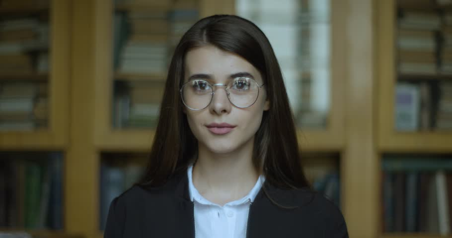 Female student, library. Girl looks straight in the camera and smiles | Shutterstock HD Video #1023229360