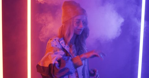 Cheerful stylish blonde girl in hat and sunglasses dancing and smiling in the smoke and neon lights.