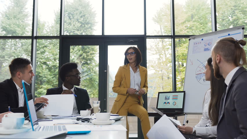 Young business woman gives presentation to multi-ethnic business group, coaching employees, explaining project charts on whiteboard and laptop, speaking about new marketing plan and new arrivals of | Shutterstock HD Video #1023252550