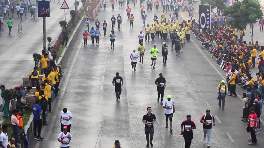 Mumbai, Maharashtra India - January 20th 2019 : Overview shot of a crowd of 100s of people running on the streets of Marine Drive for Tata Mumbai Marathon TMM2019 on a cold foggy winter morning. #1023267760