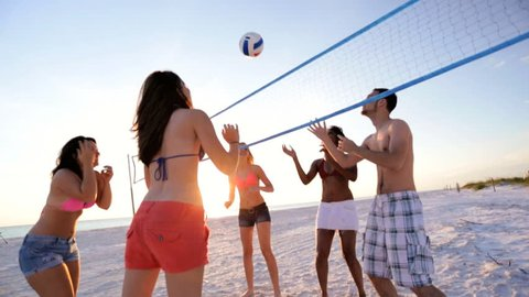 9d696a74657 Young multi ethnic people wearing bright clothing enjoying time together playing  beach volleyball weekend break