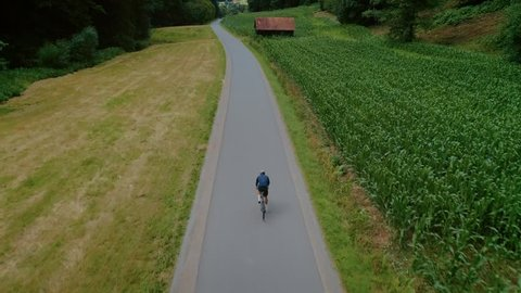 Epic aerial drone footage of professional cyclist riding down beautiful countryside road between fields and forest. Atheltic training or strength workout on sunny summer day. Healthy cycling lifestyle