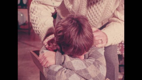 1970s: UNITED STATES: boy hugs self and cries. Man tells boy not to cry. Relative pats teenager on head.