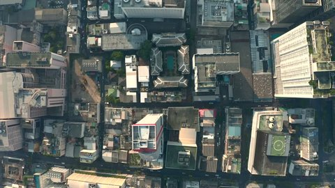 Aerial city view of Bangkok with crossroads and roads, houses, buildings and parking lots. Helicopter drone shot.