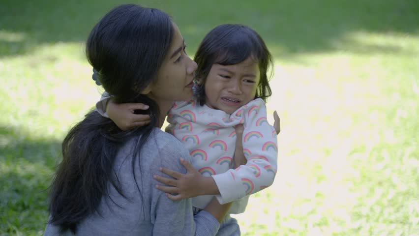 portrait of asian mother telling her upset daughter to stop crying