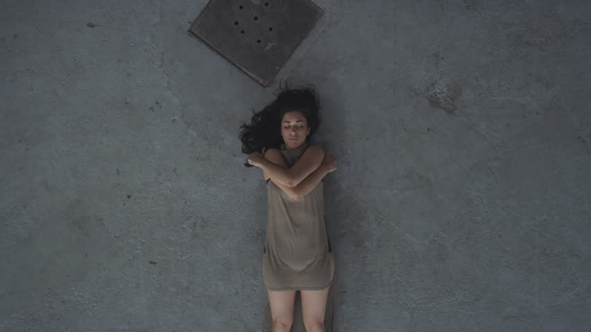 Dancer asleep on concrete floor in industrial warehouse opening eyes looking into camera and standing up. Overhead shot filmed with RED Dragon 6K camera | Shutterstock HD Video #1023446290
