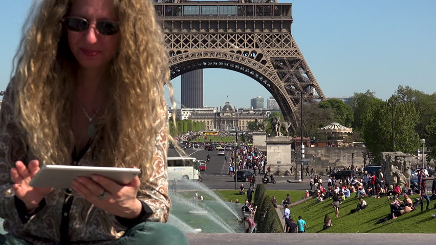 Beautiful woman with hair in the wind captures moments and memories near the Eiffel Tower | Shutterstock HD Video #1023462310