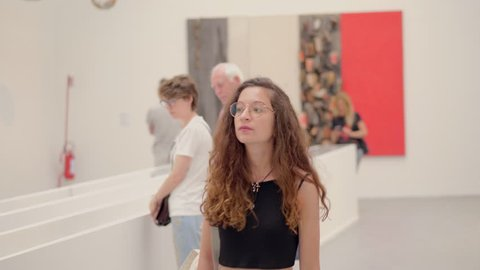 young woman looks at the works exhibited in a contemporary art museum