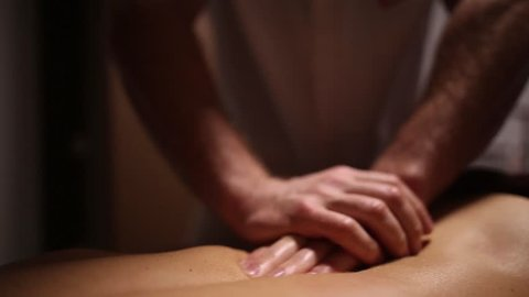 Young woman gets massage with oil for back in the spa