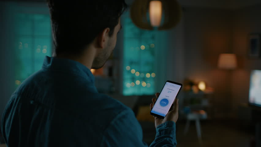 Young Handsome Man Gives a Voice Command to a Smart Home Application on His Smartphone and Lights in the Room are Being Turned On. He is Impressed by Technology. It's a Cozy Evening. | Shutterstock HD Video #1023495730