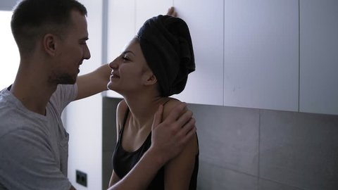 Young romantic couple on the kitchen. Sexy young woman is sitting on the counttable in domestic clothes and bath towel on head and hugging her handsome man. Spending time together, hugging. Passionate