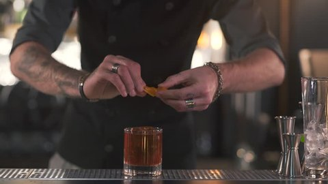 Unrecognizable bartender squeezes orange rind into a glass with a cocktail, then puts the rest into the glass close up. Bartender making alcoholic cocktail in modern bar